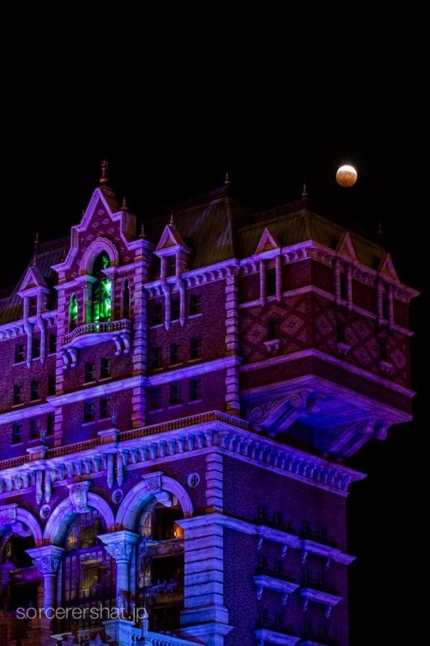 緑色に光るタワー・オブ・テラーと月食の月
